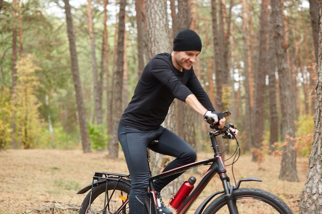 Outdoor shot of young handsome man riding bicycle on nature
