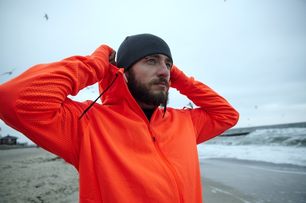 Outdoor shot of young pretty bearded male with eyebrow piercing holding raised hands behind his head and looking ahead with folded lips, enjoying seaside view after morning workout