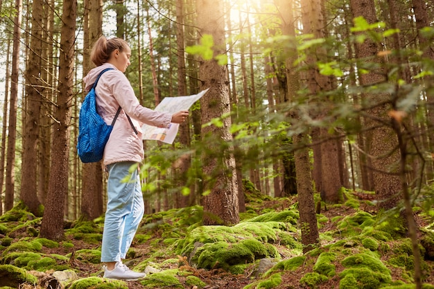 Outdoor shot of young slender backpacker being inspired by travelling, enjoying active rest, holding map, following trip way, good at orientating, wearing casual clothes. leisure activities concept.