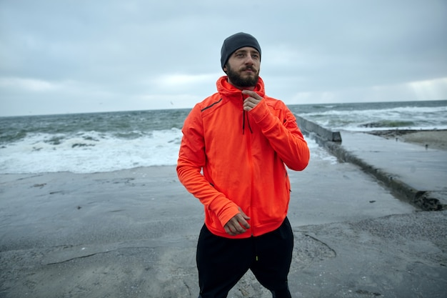 Outdoor shot of young sporty dark brunette man with lush beard posing on coastline of sea over cold early morning, preparing for everyday workout and looking ahead with calm face
