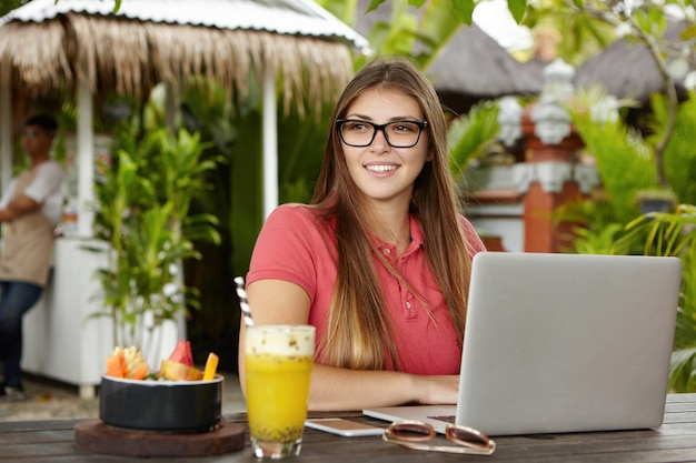Outdoor shot of young woman blogger wearing polo shirt and rectangular glasses sitting in front of open laptop computer