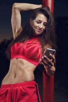 Спорт на открытом воздухе красивая сильная сексуальная спортивная мускулистая молодая кавказская фитнес-женщина с тренировкой по мобильному телефону в тренажерном зале на диете, накачивая пресс, позирует, концепция бодибилдинга