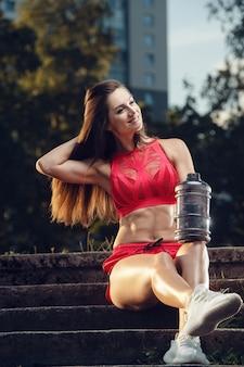 Спорт на открытом воздухе красивая сильная сексуальная спортивная мускулистая молодая кавказская фитнес-женщина с бутылкой воды, пьющей на тренировке