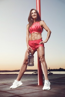 Outdoor sport beautiful strong sexy athletic muscular young caucasian fitness woman with water bottle drinking at workout training in gym on diet