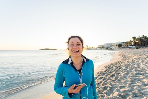 야외 스포츠, 피트니스 가제트, 사람들의 개념 - 이어폰을 끼고 스마트폰을 들고 웃고 있는 여성 피트니스.