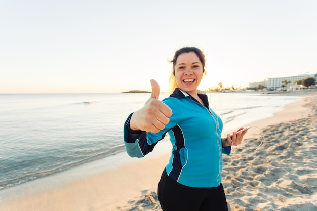 야외 스포츠, 피트니스 가제트, 그리고 사람들의 개념 - 웃는 여성 피트니스는 엄지손가락을 치켜들고 이어폰을 끼고 스마트폰을 들고 있습니다.