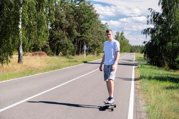 アウトドアスポーツ。若い男が森の真ん中にある道をスケート
