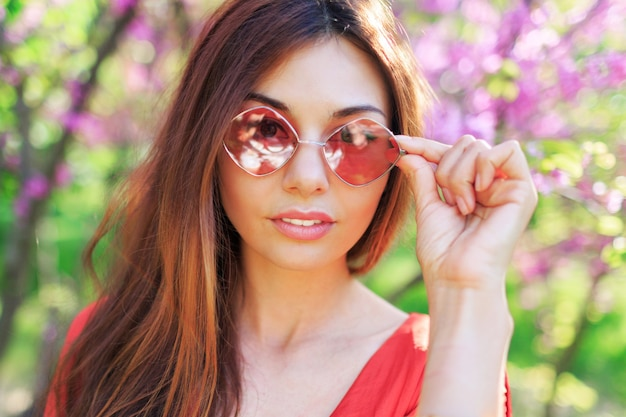 Outdoor spring close up portrait of brunette woman enjoying flowers in sunny blooming garden.