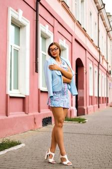 Открытый уличный модный взгляд на элегантную гламурную сексуальную девушку в стильном мини-платье и небесно-голубом жакете.