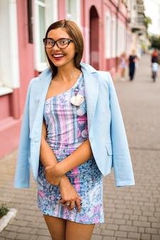La moda street style all'aperto guarda una ragazza sexy glamour elegante, che indossa un mini abito di classe e una giacca celeste