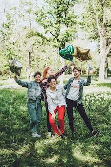 Открытый студенческий вечер. группа улыбающихся веселых подруг, празднующих вечеринку с воздушными шарами в парке