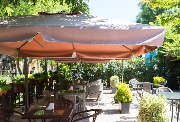 Outdoor summer cafe with umbrella and flower beds