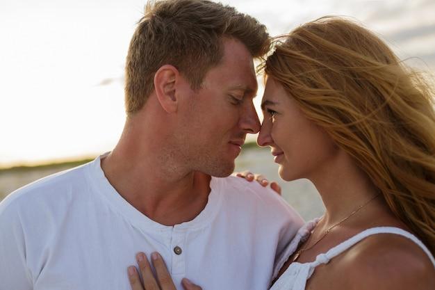 ビーチで若い美しいスタイリッシュなカップルの屋外夏のクローズアップの肖像画。