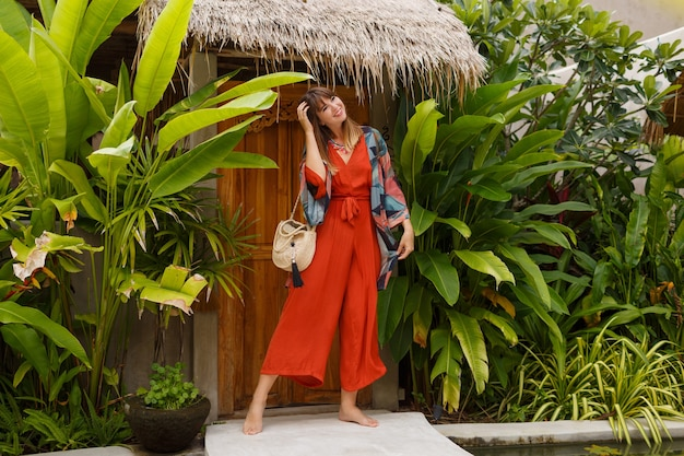 Outdoor summer fashion photo of gorgeous woman in boho   outfit posing in tropical luxury resort.  full lenght. tropical plants.