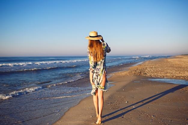 孤独なビーチ、トーンの色、リラックスした贅沢な休暇で海の近くでポーズをとる金髪モデルの屋外夏のファッションの肖像画