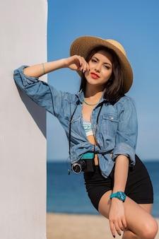 Открытый летний модный портрет великолепной женщины с загорелым телом, полными красными губами и длинными сильными ногами, позирующими на тропическом солнечном пляже.