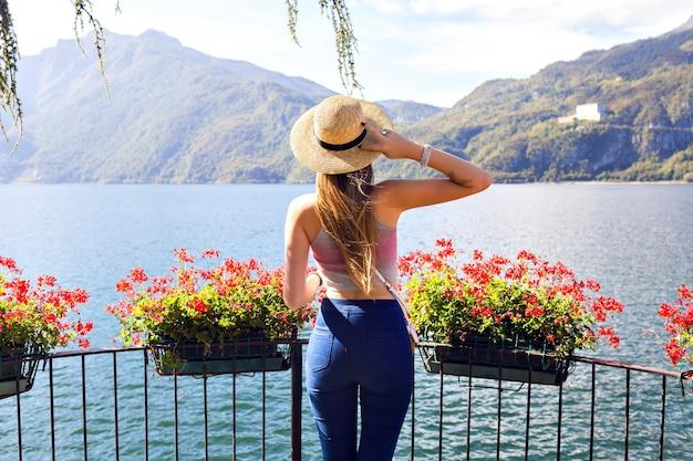Открытый летний модный портрет стильной женщины позирует возле пальм и наслаждается экзотическим отдыхом