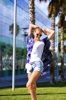 Outdoor summer fashion portrait of stylish woman posing near palm trees, enjoy exotic vacation, casual outfit, boots and sunglasses, bright colors, travel at barcelona, bright colors, street style.