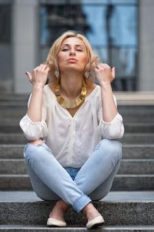 꽤 젊은 금발의 섹시 한 여자의 야외 여름 패션 멋진 초상화는 흰 셔츠와 거리에서 포즈 찢어진 청바지를 입고.