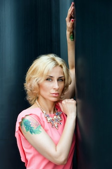 꽤 젊은 금발의 섹시 한 여자의 야외 여름 패션 멋진 초상화 거리에서 포즈를 취하는 짧은 핑크 드레스를 입고.
