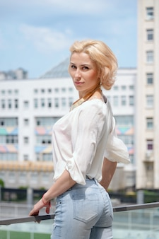 Outdoor summer fashion stunning portrait of pretty young blonde sexy woman dressed in a white shirt and torn jeans posing in the street.