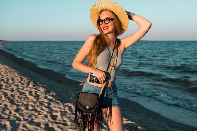 Immagine estiva all'aperto di bella donna bionda in cappello di paglia che cammina vicino al mare.
