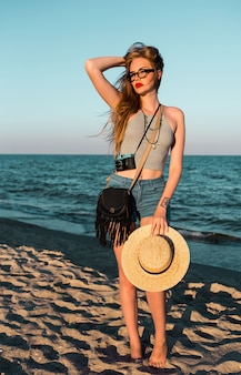 Outdoor summer image of beautiful blond woman in straw hat walking near the sea.