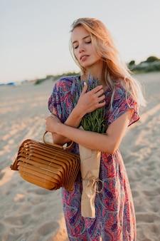 Immagine estiva all'aperto di bella donna bionda romantica in vestito colorato che cammina sulla spiaggia con bouquet di lavanda.