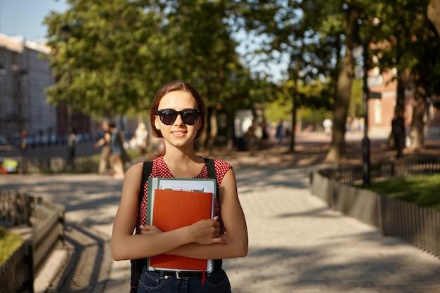 Летнее изображение очаровательной симпатичной кавказской студентки в стильных очках, рюкзаке, топ в горошек и джинсах, идущей в колледж пешком, несущей тетради, улыбающейся и наслаждающейся хорошей погодой на открытом воздухе
