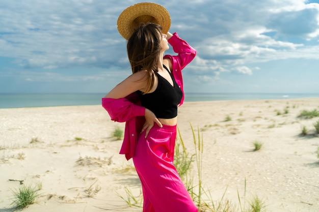 ビーチでポーズをとるスタイリッシュなブルネットの旅行女性の屋外夏の画像。スタイリッシュなピンクの衣装を着ています。麦わら帽子。
