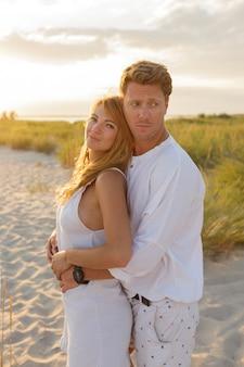 Открытый летний образ молодой красивой стильной пары на пляже.