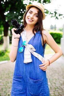 街で楽しんでいるかなり若い女性の屋外の夏のライフスタイルの肖像画。流行に敏感なスタイルのメガネと帽子で写真を作る写真家。