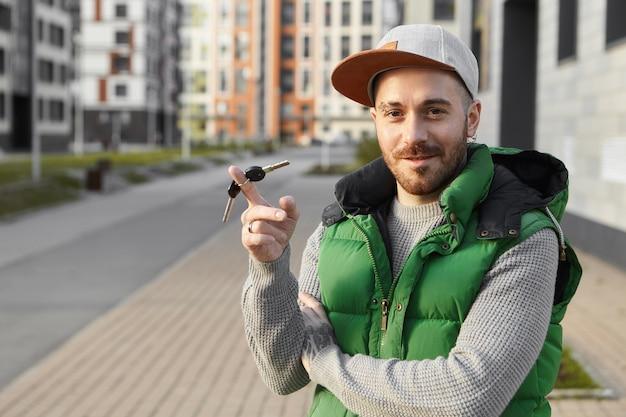 쾌활한 자신감 표정을 가진 기뻐 잘 생긴 젊은 수염 난 남자의 야외 여름 사진, 웃고, 검지 손가락 주위에 열쇠를 비틀고, 새 차, 아파트, 야외 서 자랑