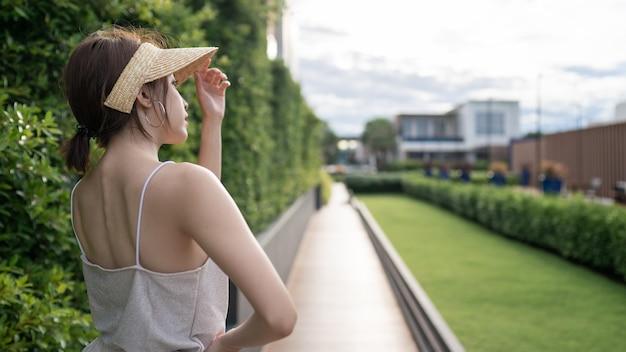 Открытый летний портрет вид сзади женщины с соломенной шляпой на дороге и зеленом саду