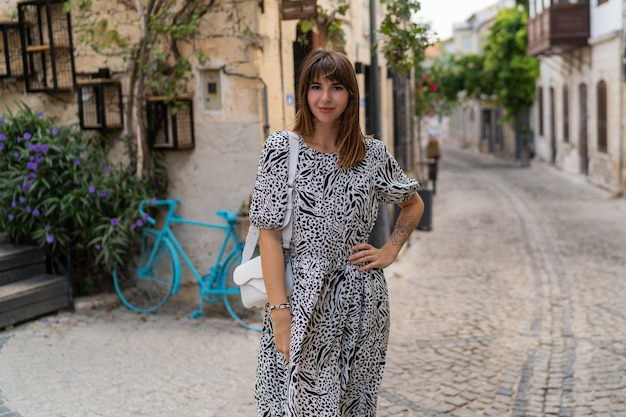 Outdoor summer portrait of beautiful woman wolking in old european city.