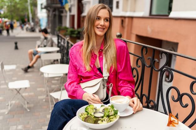 Ritratto estivo all'aperto di una donna bionda allegra che si gode il suo gustoso brunch al bar con terrazza della città.