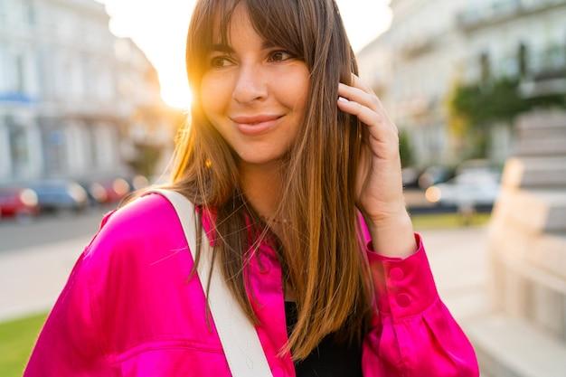 Outdoor summer portrait of debonair good-looking woman in stylish pink jacket.