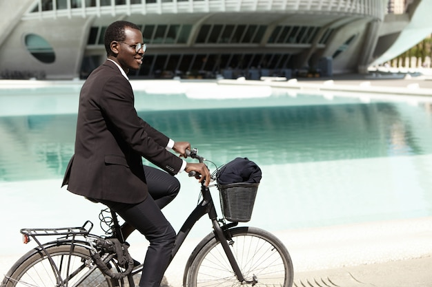 Outdoor summer portrait of handsome young black european office worker in sunglasses cycling on his bike to work in urban surroundings on, having fun, feeling carefree and relaxed expression