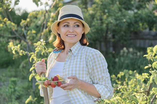 Outdoor summer portrait of mature positive woman in straw hat on nature
