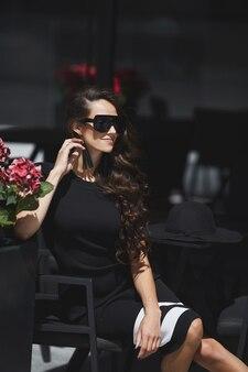 ヨーロッパの都市の通りのカフェテーブルに座っている流行のサングラスとファッショナブルなドレスを着ているモデルの女性の屋外の夏の肖像画