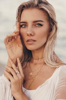 海の近くのビーチで身も凍るように美しい幸せな金髪女の夏の屋外の肖像画