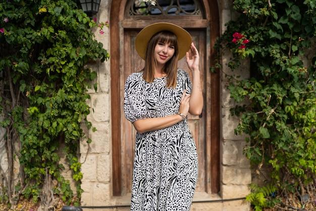 Открытый летний портрет красивой женщины wolking в старом европейском городе. в соломенной шляпе.