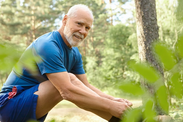 Открытый летний портрет красивого харизматичного небритого пожилого мужчины в шортах и футболке, улыбающегося, стоящего на пне и завязывающего шнурки на кроссовках.