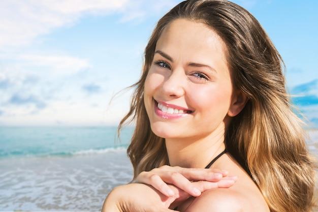 바다 근처에서 포즈를 취하는 꽤 젊고 웃는 행복한 여성의 야외 여름 초상화