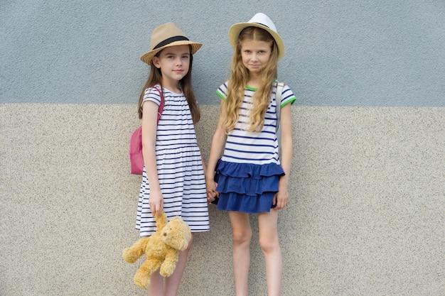 手を繋いでいる2つの幸せなガールフレンドの屋外夏の肖像画。