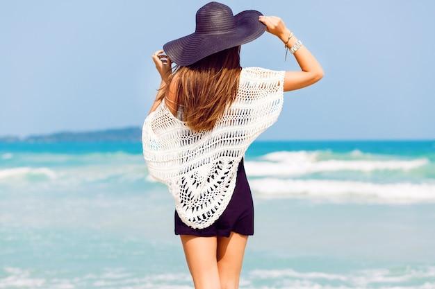 熱帯のビーチで海を見ている若いきれいな女性の屋外の夏の肖像画は、スタイリッシュな帽子と服を着て、彼女の自由と新鮮な空気をお楽しみください