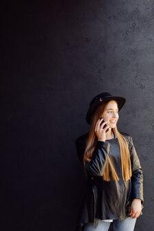 휴대 전화와 함께 거리에 화창한 날에 포즈 젊은 세련된 여자의 여름 야외 초상화