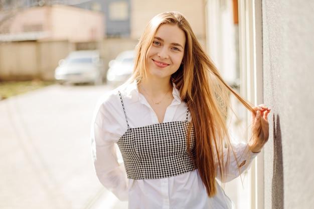 通りで晴れた日にポーズをとった若いスタイリッシュな女の子の屋外夏の肖像画
