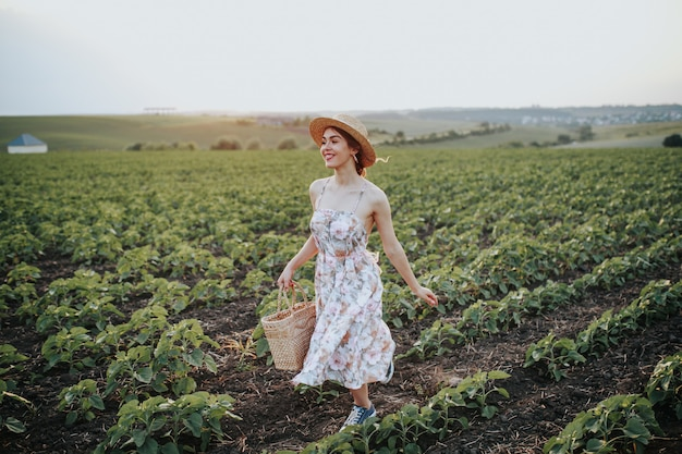 Outdoor summer portrait of teen girl with basket strawberries, straw hat. a girl on country road, back view. nature background, rural landscape, green meadow, country style