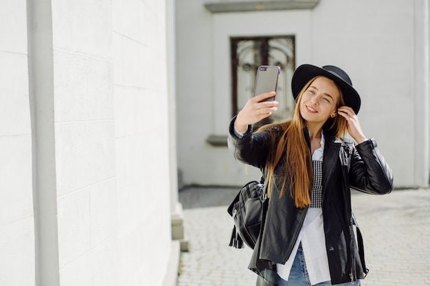 Outdoor summer portrait of young stylish girl posed in sunny day on street with phone